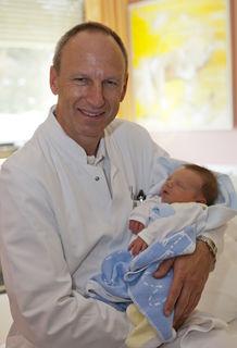 Primar Burghard Abendstein mit einem Neugeborenen