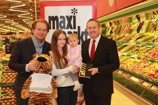 Jasmin Huber mit Töchterchen Amelie bei der Gewinnübergabe mit Thomas Reiter (Marketing-Leiter BezirksRundschau) und Thomas Schrenk (Geschäftsführer Maxi-Markt).