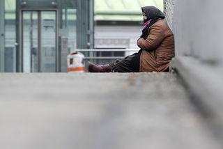 Eine Frau bettelt auf dem Fußgängerübergang bei der U-Bahnstation Hütteldorf.