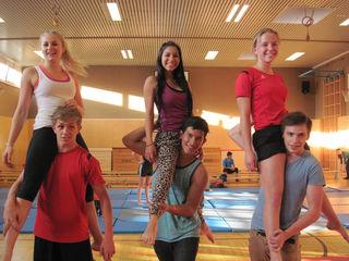 """Schüler des BORG Honauerstraße probieren mit Mitgliedern des """"Circo Fantazztico"""" eine Akrobatiknummer: Philipp und Hannah, Jeudy und Eli aus Costa Rica, Benjamin und Sarah (v.l.)"""