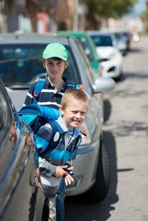 Wegen der vielen abgestellten Autos gehen viele Kinder an der rechten Fahrbahnseite zur Schule.