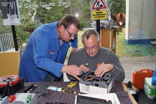 Georg und Christian versuchen einen in die Jahre gekommenen Diaprojektor zu reparieren.
