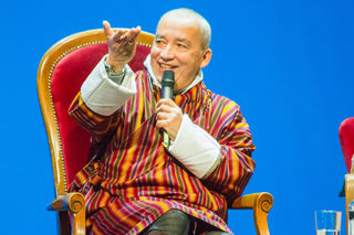 Der bhutanesische Glücksbeauftragte Ha Vinh Tho während der Diskussionsveranstaltung auf dem Gemeinwohl-Fest im Wiener Volkstheater