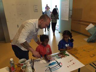 Daniel Merkl malt gemeinsam mit zwei Kindern aus der Flüchtlingsunterkunft an einem Bild.