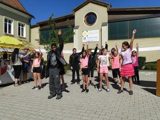 """""""Grease"""" - ein Tanz der 1c-Klasse am Beginn des Festes vor den internationalen Spruchbändern."""