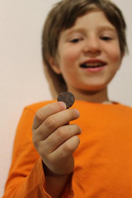 Jakob Steinacher hält mit Stolz einen entdeckten Römerschatz in der Hand.