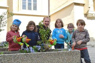 Schon jetzt freuen sich Martin Kögler und die KIKO-Kids auf Himbeeren, die im Sommer im Hochbeet wachsen werden.