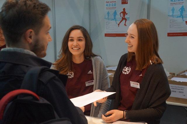 Emelie-Luise Lang (Mitte im Bild) und Juliane Prüfert (rechts) sind beide Schülerinnen der 4BK (4. Klasse HAK) der Vienna Business School Mödling) und arbeiten bereits zum zweiten Mal begeistert in der Startnummernausgabe beim Vienna City Marathon mit.