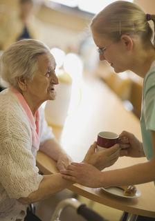 Altenheim, Pflegerin gibt Seniorin eine Tasse