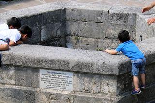 Türkenbrunnen, Schloßberg Graz, durch das Eisengitter können die Kinder in die Tiefe schauen