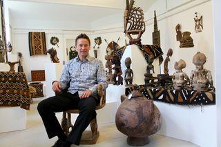 Galerist Alexander Schwaighofer neben einem Äthiopischen Honigtopf, der aus einem einzigen Stück Holz gefertigt wurde