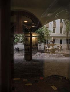 Spiegelung im Haustor des Hundertwasserhauses mit Blick zum aus fünf Teilen zusammengesetzten Brunnen nach klassischem römischen Vorbild.