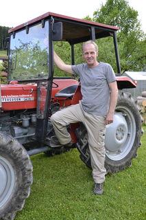 Schärdings Bezirkspolizeikommandant Matthias Osterkon in ungewohnter Pose – vor seinem Traktor für die Waldarbeiten.