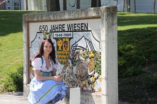 Ein Bild, das zusammengehört: die Erdbeerkönigin und das Wappen ihrer Heimatgemeinde