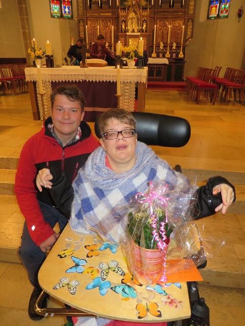 Schulsprecher Jonas Wagner übergab im Namen seiner Mitschüler der NMS Bad Leonfelden beim Ostergottesdienst den Gutschein und Blumen an Sarah Bacher.