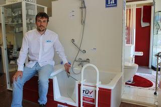 Matthias Marvan zeigt die Badewannen-Türe, die sich individuell einbauen lässt.