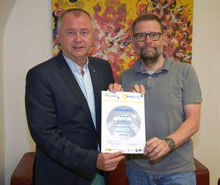 """Hans Stefan Hintner (links) und Gerhard Wannenmacher präsentieren die Nominierungs-Urkunde für das E-Carsharing-Projekt """"E-Carregio""""."""