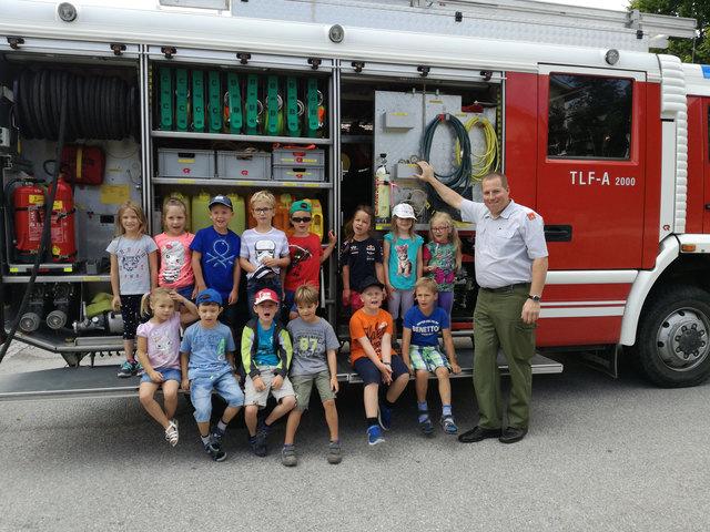 Die Kinder lernten die Ausrüstung der Feuerwehr näher kennen. Rechts: Kommandant Mario Schmidberger