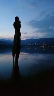 Die Skulptur von Bruno Cappelletti und der Stubenbergsee in der Abenddämmerung.