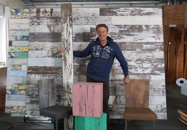 Firmenschef Arno Stainer mit einer Original-Holzlatte vor den Reproduktionen
