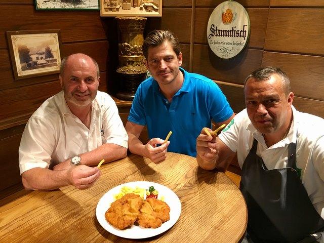 Gemeinsam mit Bürgermeister Josef Balber und dem Wirten Gustav Fischer genießt Kozar die (noch) knusprigen Pommes im Gasthaus zur Linde in Hafnerberg.