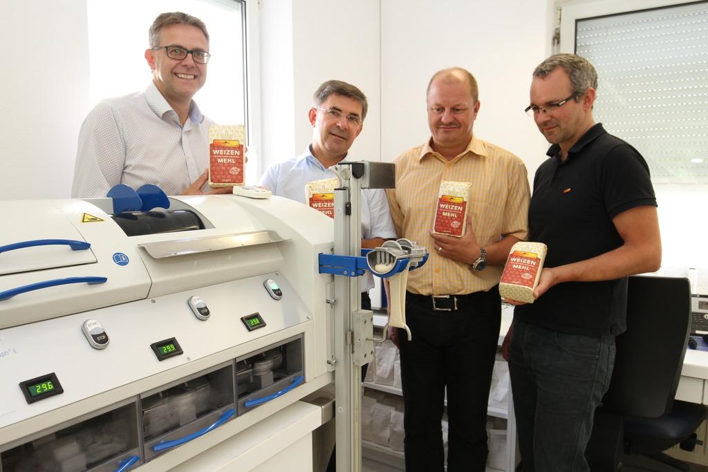 Bernhard Gitl, Franz Fartek, Heinz Hopfer und Michael Fend vor der Maschine, die die Teigeigenschaften des Weizenmehls prüft.