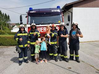 Erleichtert, dass sie wieder im Freien ist: Die kleine Theresa (Mitte) mit ihren Rettern von der Feuerwehr Sierning.