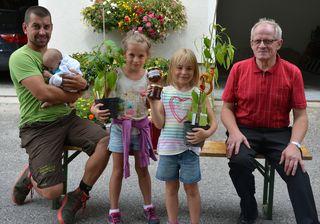 Der Fleiß wurde mit einer Gemüsepflanze und einem selbst abgezapften Honig belohnt! Am Bild: Daniel Viehböck mit Tochter Klara, Kinder vom Ferienprogramm, Imker Karl Viehböck.