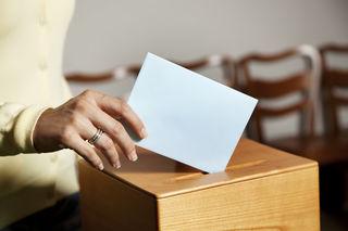 Eine junge Frau bei einer Wahl in der Wahlzelle. Stimmabgabe in der Demokratie