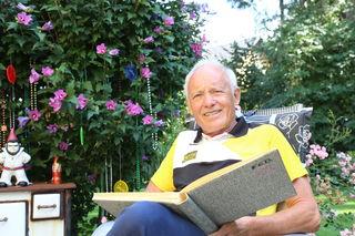 Wolfgang Neffe blättert in seinem Garten durch die Fotoalben.