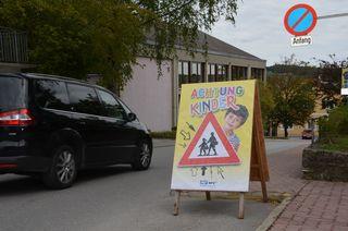 """Vor den steirischen Schulen ist nun zu Schulbeginn ein """"Achtung Kinder"""" Plakat zu finden und macht verstärkt auf das Schulumfeld bemerkbar."""