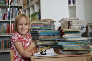 Leseratte Marie Heinzl mit etwa der Hälfte der Bücher, die sie in den Ferien gelesen hat.