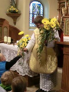 Kinder überreichen dem Herrn Pfarrer Blumen (jedes Kind eine)