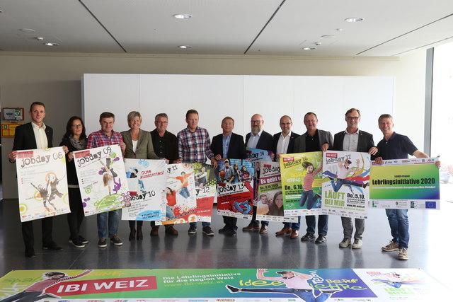 Vertreter der Lehrlingsinitiative und einige teilnehmende Betriebe halten die Plakate der letzten zehn Jahre des Jobdays hoch.
