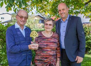 """Kürzlich feierten Edith und Friedrich Breitfuss aus der Gemeinde Wals-Siezenheim (Ortsteil Schweizersiedlung) das Jubiläum der Goldenen Hochzeit. Bürgermeister Joachim Maislinger gratulierte den Jubilaren und überreichte als Ehrengeschenk den """"goldenen Birnbaum"""" der Gemeinde Wals-Siezenheim."""