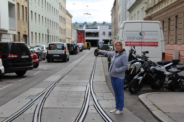 Bezirksvorsteherin Stellvertreterin Katharina Krammer zeigt, dass hier die Parkplätze wegen eines zweiten Gleises verschwinden könnten.