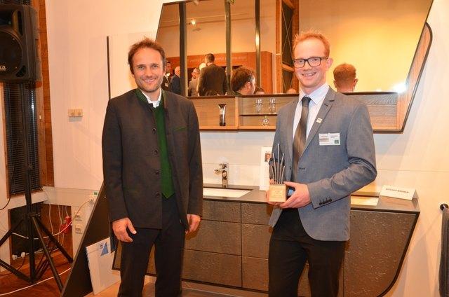 """Günther Kamml von der Firma Leitz mit """"Lokalmatador"""" Markus Hamedinger aus St. Roman. Im Hintergrund ist sein Waschtisch mit Spiegelelement zu sehen, der die Besucher begeisterte und ihm den Publikumspreis – einen Golddukaten – sicherte."""