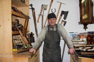 Alexej Sevcik in seiner Messerschmiede - die schönen, alten Äxte und Hacken hinter ihm hat er liebevoll restauriert