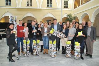 Die Projektbeteiligten mit Partnern präsentieren die Postkarten in der FH Spittal