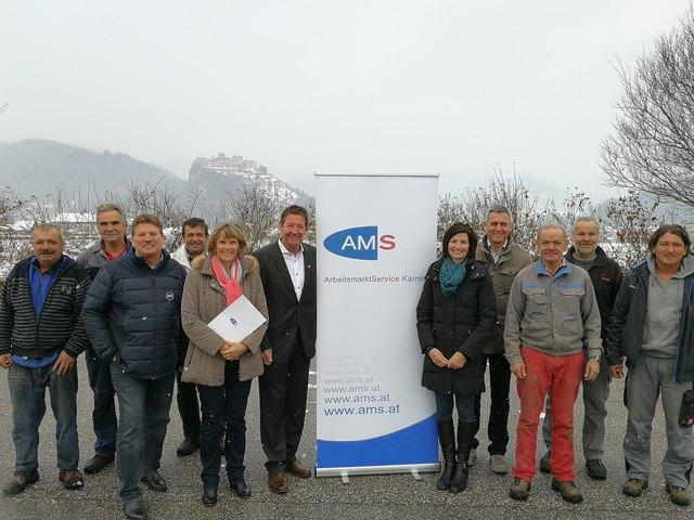 Bürgermeister Josef Müller (links neben dem Rollup) und Helena Wutscher-Grünwald vom AMS (links) beim Abschluss des Projektes