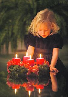 Ein kleines Mädchen mit einem Adventkranz mit 4 Kerzen am letzten Adventsonntag freut sich auf Weihnachten