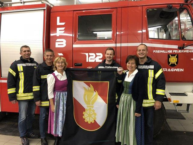 Die Kameraden der FF- Tragwein Dieter Penn, Franz Aigner, Willi Schmalzer mit Kommandant Daniel Schützenhofer freuen sich über die neuen Fahnen die von Marianne Schützenhofer und Martha Hinterdorfer überreicht wurde.