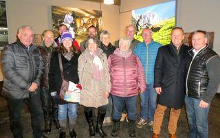 Gruppenfoto von allen abgebildeten Bauern sowie Bürgermeister Klaus Manzl (links), Fotograf Michael Eppensteiner (3.v.r.), Aufsichtsratsvorsitzender Hannes Winkler (2.v.r.) und Bergbahn Geschäftsführer Klaus Exenberger (rechts) vor einigen der Bilder.