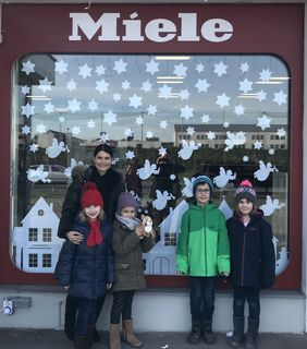 Emma Zloklikovits, Sophie Horl, Fabian und Amelie Mittl (von links) mit Lehrerin Elisabeth Leitgeb vor dem dekorierten Fenster der Firma Haustechnik Güssing.