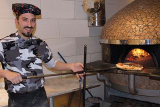 Luigi Mario De Felice  schiebt nur nach streng neapolitanischer Tradition zubereitete Pizza in den Ofen.