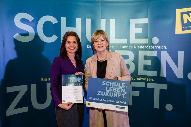 """Foto: Bildungslandesrätin Barbara Schwarz überreicht VD Maschek die Plakette """"Wir sind Lebensraum Schule"""""""