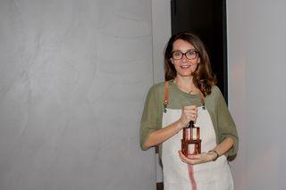 Doris Pesendorfer in einer Leinenschürze mit einem Kupferstempel aus ihrer Raw&Order Kollektion