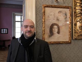 Georg Hamann im Salon vor einem Bild, auf dem drei Generationen rund um Joswefine Wertheimstein festgehalten sind.
