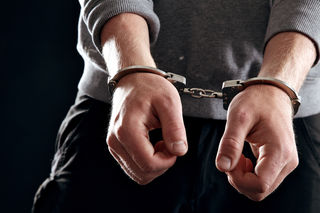 Offender with his hands in handcuffs