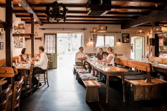 Der gemütliche Gastraum des Kierlingers besticht durch einfache  Holztische und Bänke.